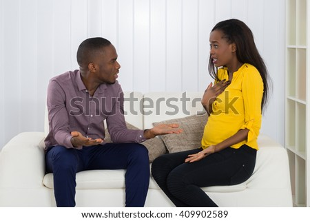 Young Couple Sitting On Sofa Quarreling With Each Other