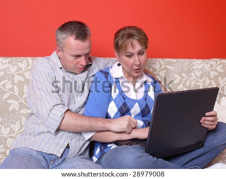 Young couple sitting on sofa using a laptop