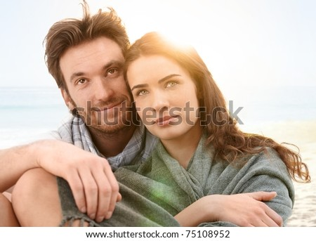 Young couple sitting on summer beach with blanket enjoying sunset.? - stock photo