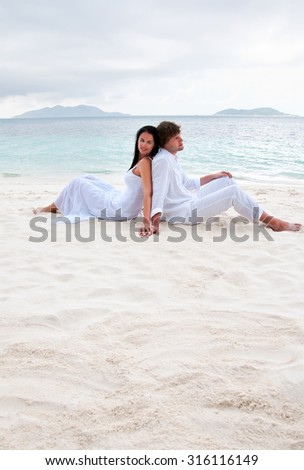 Young couple sitting on the beach near the seaside - stock photo