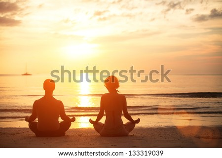 Young couple sitting on the beach of the sea in the lotus position at sunset, yoga practice - stock photo