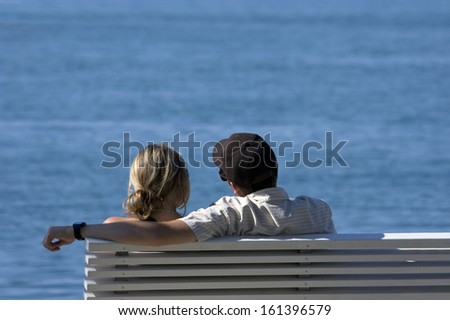 Young couple sitting on the bench on the coast with the sea in the background  - stock photo