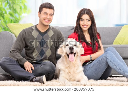 Young couple sitting on the floor with a dog at home - stock photo