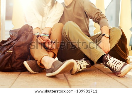 Young couple sitting on the ground in summer. Vintage sunny colors. - stock photo