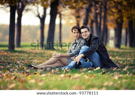 Young couple sitting on the ground in the autumn park - stock photo