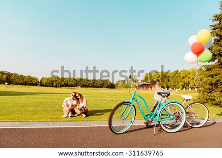 young couple sitting on the lawn near their bicycles - stock photo