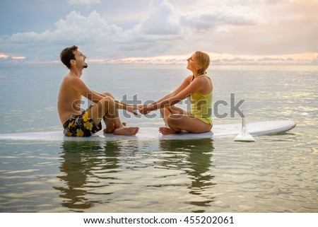 Young couple sitting on the paddle board near the beach and enjoying sunset - stock photo