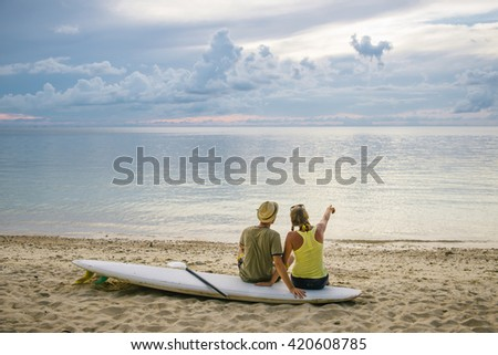 Young couple sitting on the paddle board on the beach and enjoying sunset - stock photo