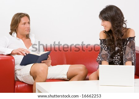 Young couple sitting on the sofa at home, he reads a book, she works  with the laptop - stock photo
