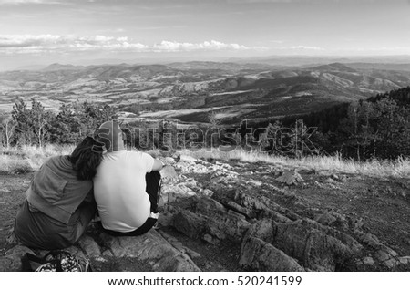 Young couple sitting on the top of the mountain on sunny summer day.