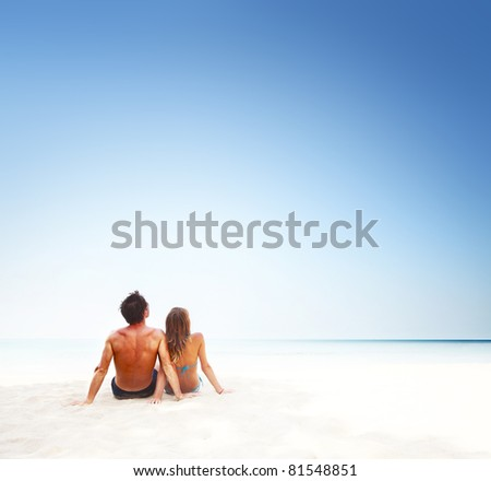 Young couple sitting on white sand by sea and enjoying each other