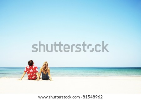 Young couple sitting on white sand by sea and looking to a blue clear sky - stock photo