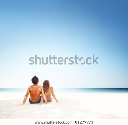 Young couple sitting on white sand by sea and looking to a sky