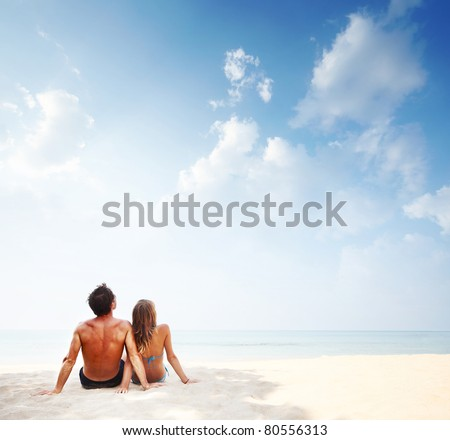 Young couple sitting on white sand of a tropical resort and looking to a blue sky - stock photo