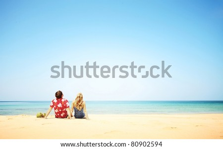 Young couple sitting on yellow sand by blue sea and looking to a clear sky - stock photo