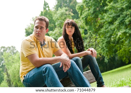 Young couple sitting outdoors on bench having relationship problems - stock photo