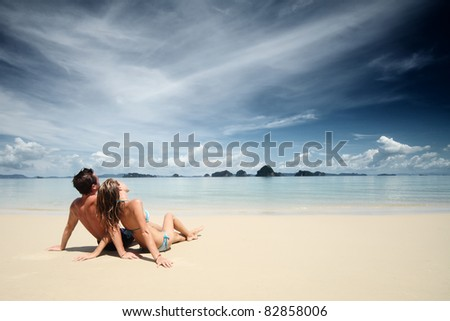 Young couple sitting together on a sand and looking to the horizon