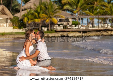 Young couple sitting together on a sand by ocean. - stock photo