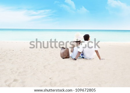 Young couple sitting together on beach. shot at tropical beach - stock photo