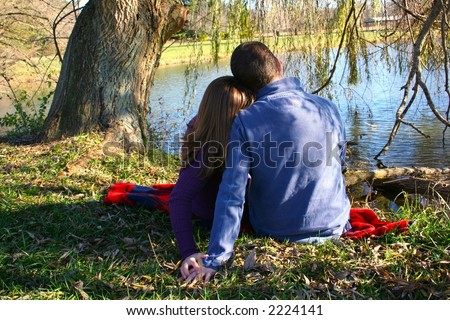 Young couple sitting under a tree - stock photo
