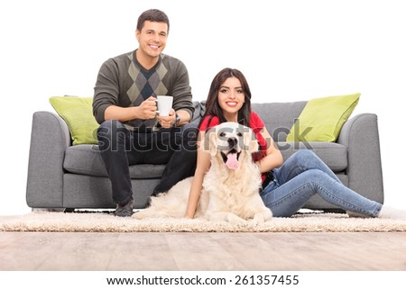 Young couple sitting with a dog on a modern sofa isolated on white background - stock photo