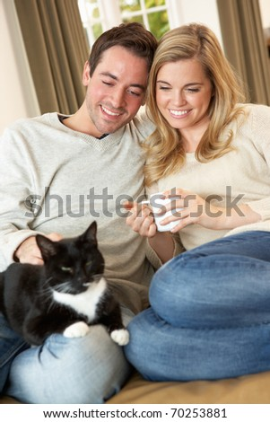 Young couple sitting with cat on sofa with cup in hand