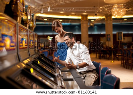 young couple sitting with cocktail, playing the slot machine - stock photo