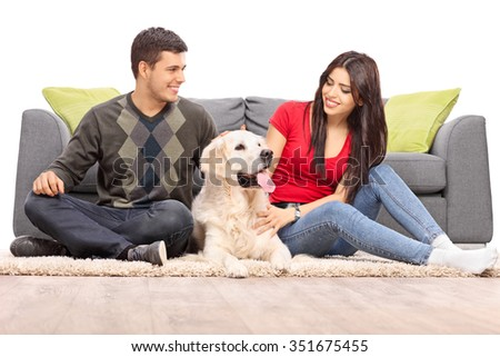 Young couple sitting with their dog in front of a gray sofa isolated on white background