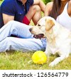 Young Couple sitting with white Dog - stock photo