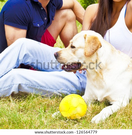 Young Couple sitting with white Dog