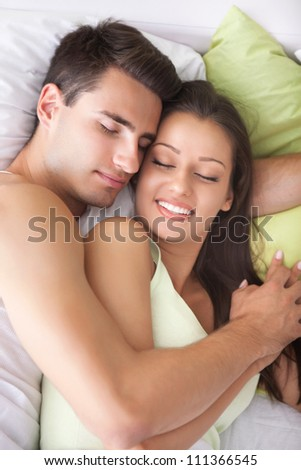 Young couple sleeping and hugging on the bed in bedroom - stock photo