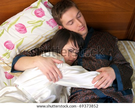 Young couple sleeping in the bed - stock photo