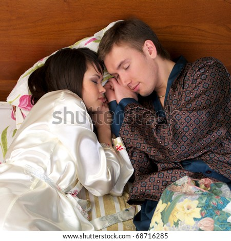 Young couple sleeping in the bed, face to face - stock photo