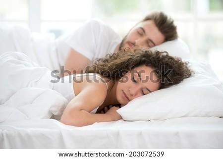 Young couple sleeping on bed - stock photo