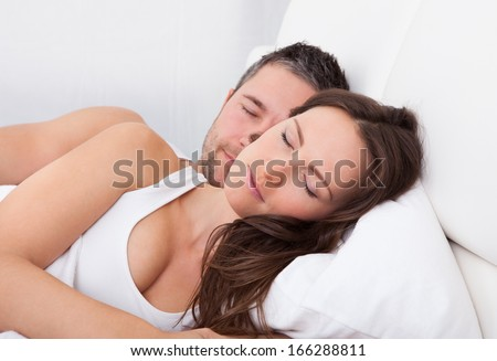 Young Couple Sleeping Side By Side On Bed - stock photo