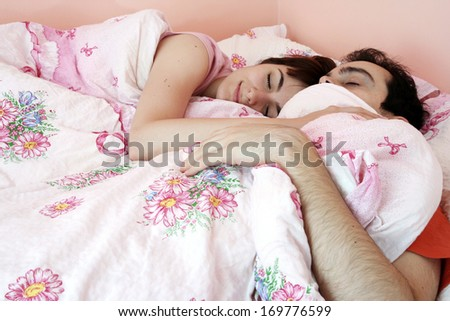 Young couple sleeping together in bed. - stock photo