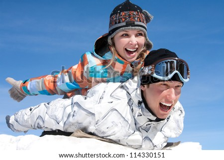Young couple slide downhill in wintertime - stock photo