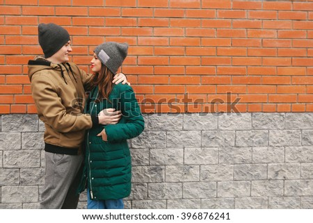 Young couple smile and hug. Casual clothes, urban, brick background. Copyspace - stock photo