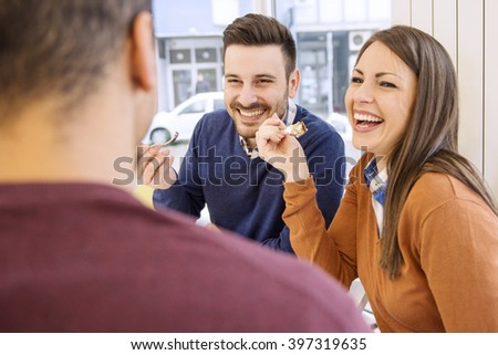 Young couple smiling and eating cake at the restaurant.Having a relaxed time together. - stock photo