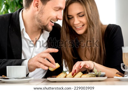 Young couple smiling and eating cheesecakes at the restaurant - stock photo