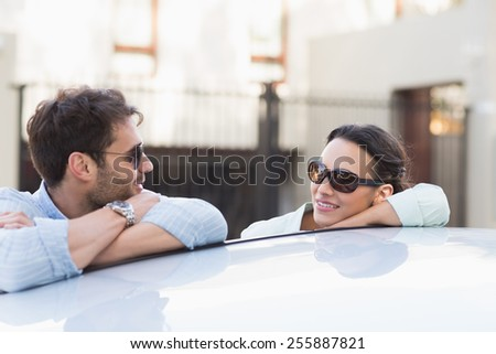 Young couple smiling at each other outside their car - stock photo