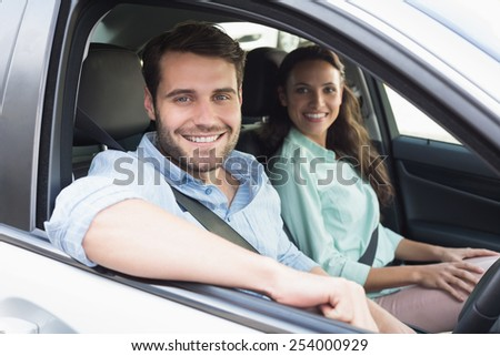 Young couple smiling at the camera in their car - stock photo
