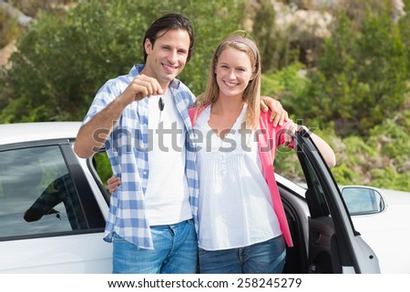 Young couple smiling at the camera outside their car