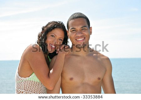 Young Couple Smiling by Water Front under Summer Blue Sky - stock photo