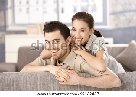 Young couple smiling happily on sofa, hugging each other at home.?