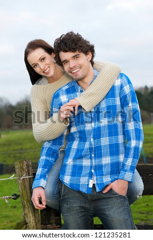 Young couple smiling outdoors. Young beautiful girl is embracing a young handsome man. - stock photo