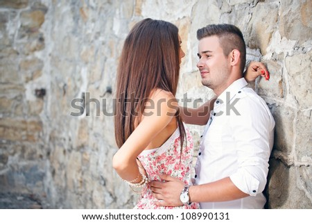 Young couple smiling while leaning on an old textured wall - stock photo