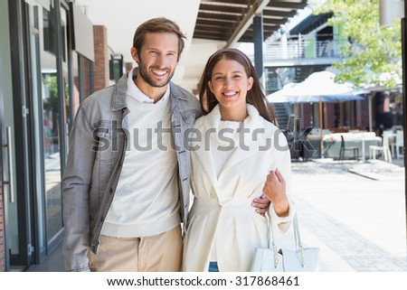Young couple smiling while walking next to a shopping mall