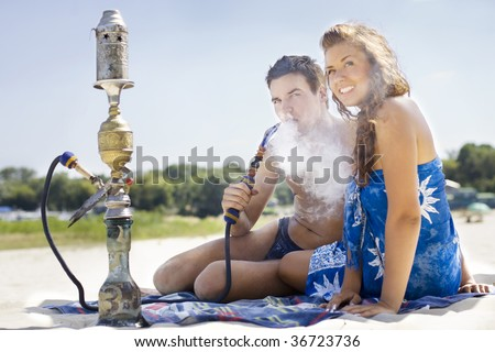 Young couple smoking hookah on the beach - stock photo