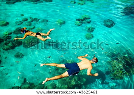 Young couple snorkeling in clean water over reef - stock photo